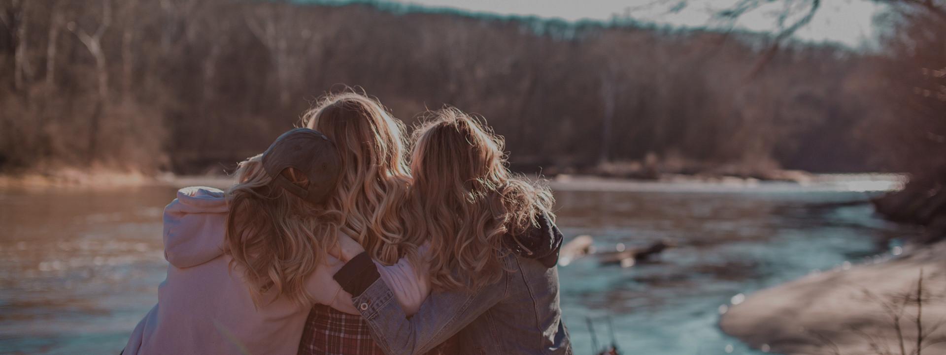 Kolme tyttöä kaulailee katsoen joelle päin.