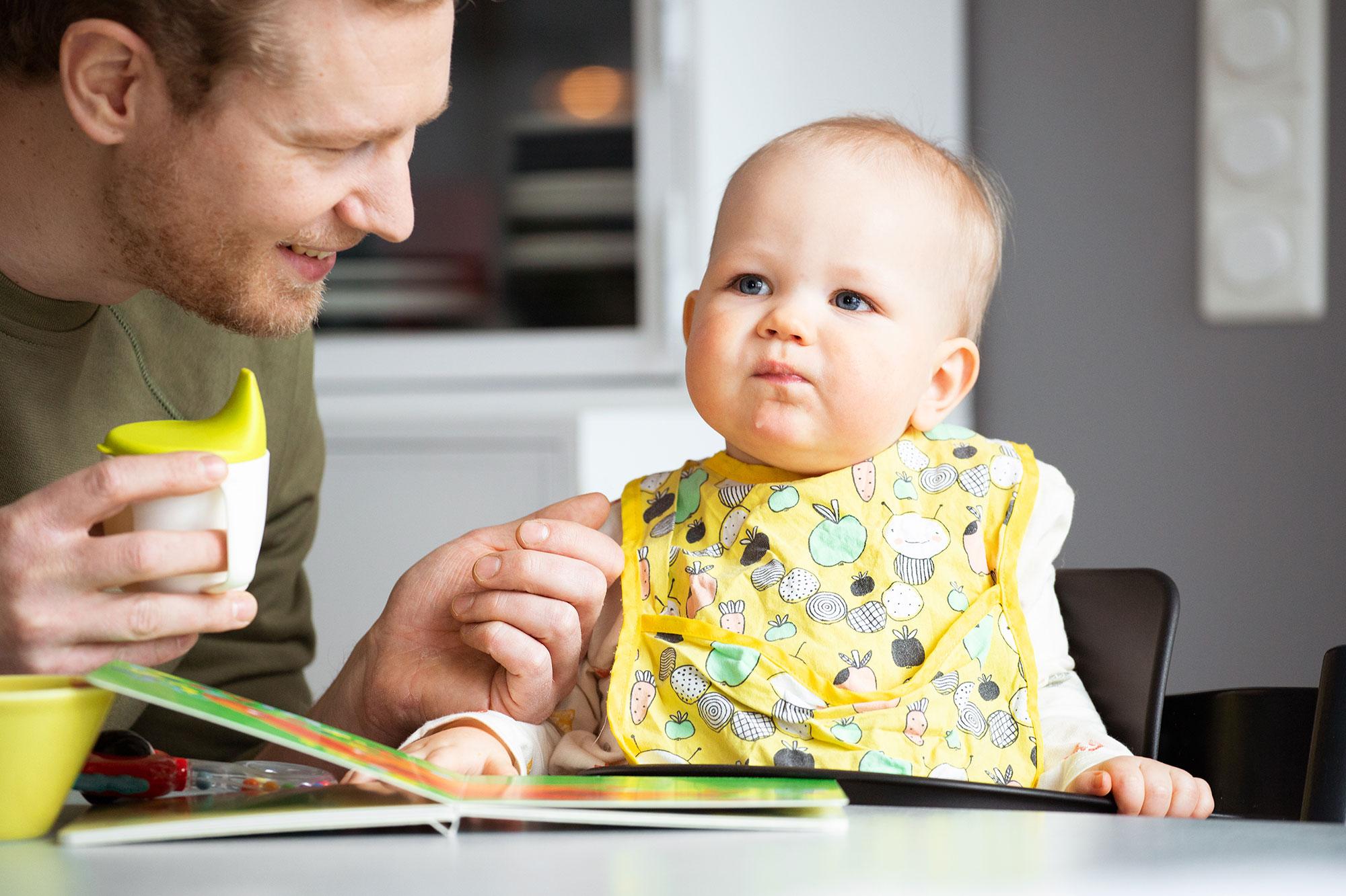 Pieni lapsi istuu ruokapöydässä ja isä juottaa juomaa nokkamukista