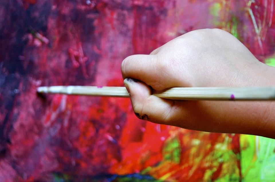 Pienen lapsen kädessä sivellin, jolla maalaa värikästä pintaa.
